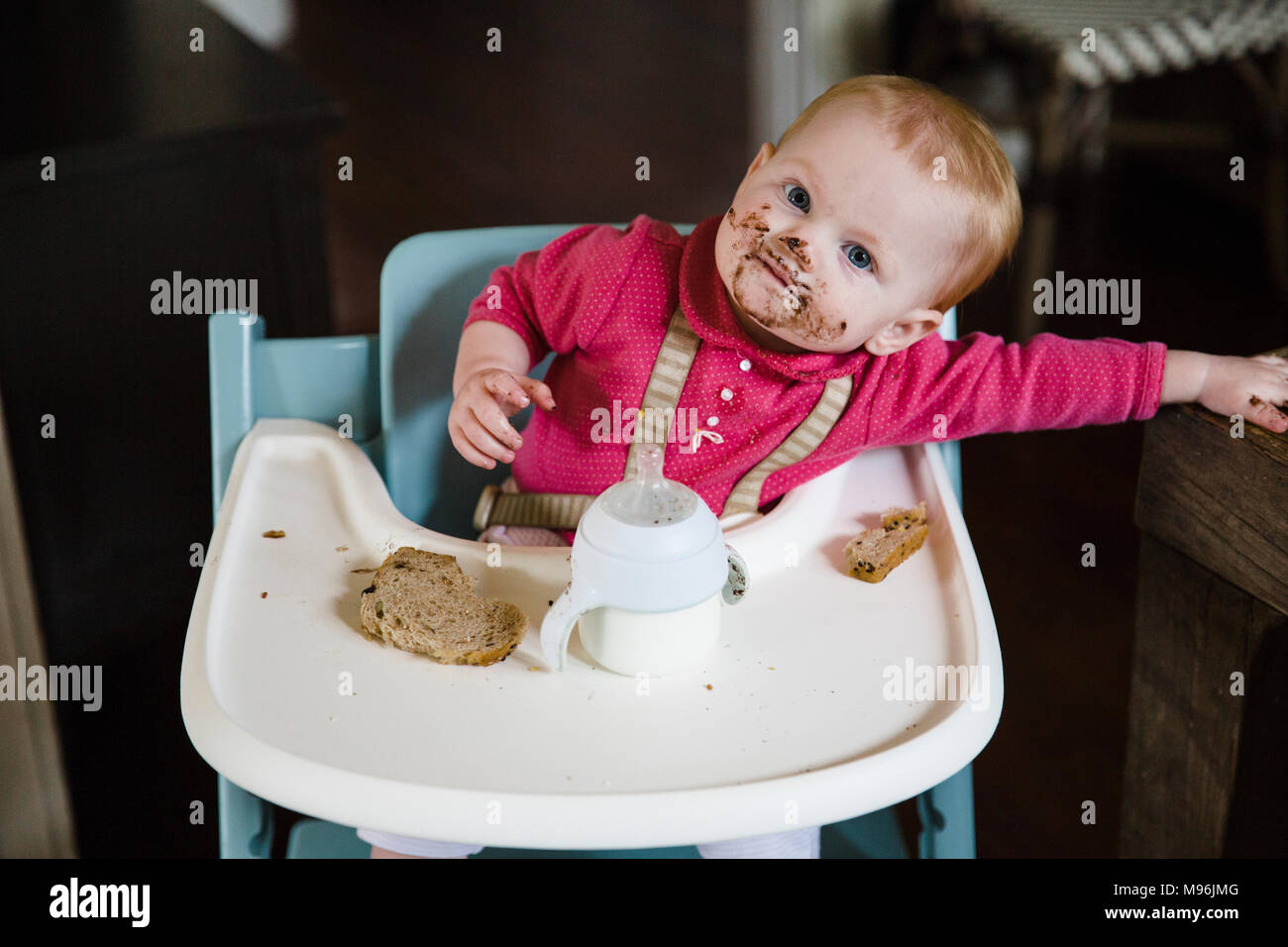 Baby in high chair with messy face eating meal - Stock Image