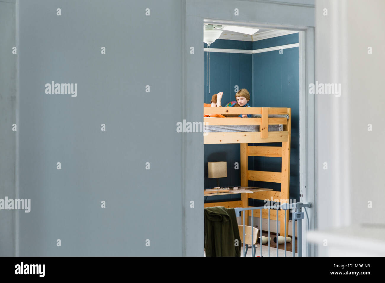 Boy on top of bunk bed reading - Stock Image