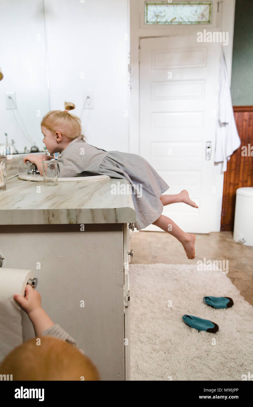 Girl reaching up to bathroom taps - Stock Image
