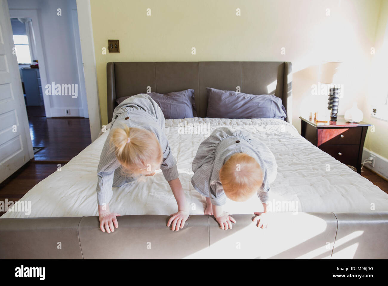 Girl and baby playing on bed Stock Photo