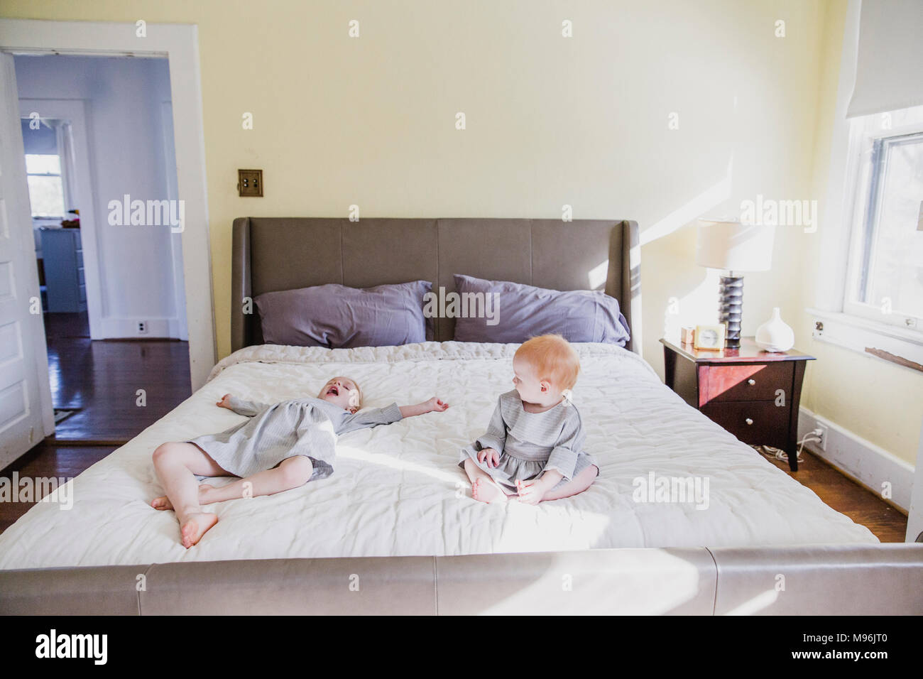 Girl and baby playing on bed - Stock Image