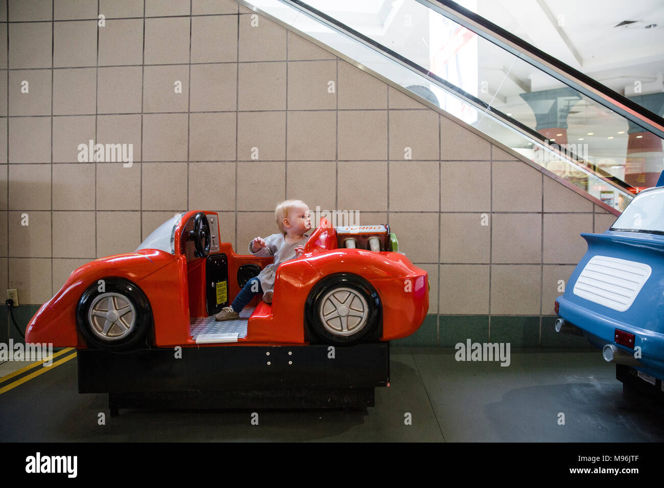 Baby sitting in car riding toy - Stock Image