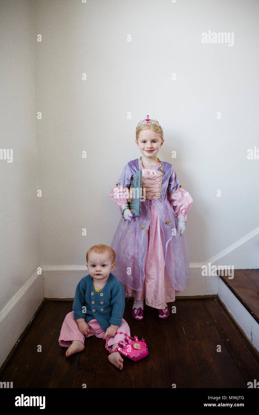 Girl in princess costume next to baby on floor - Stock Image