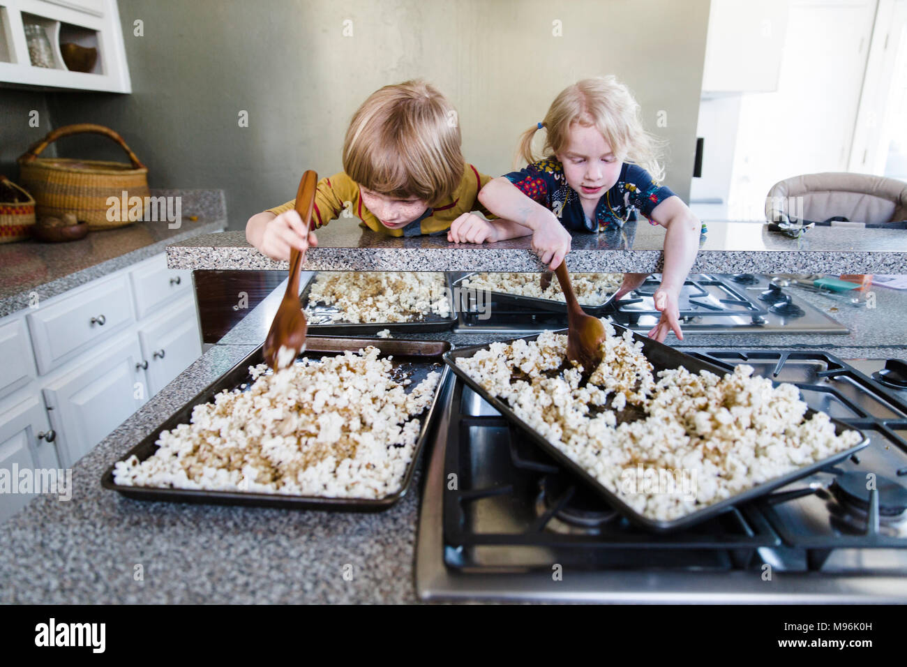 Children picking up popcorn from tray - Stock Image