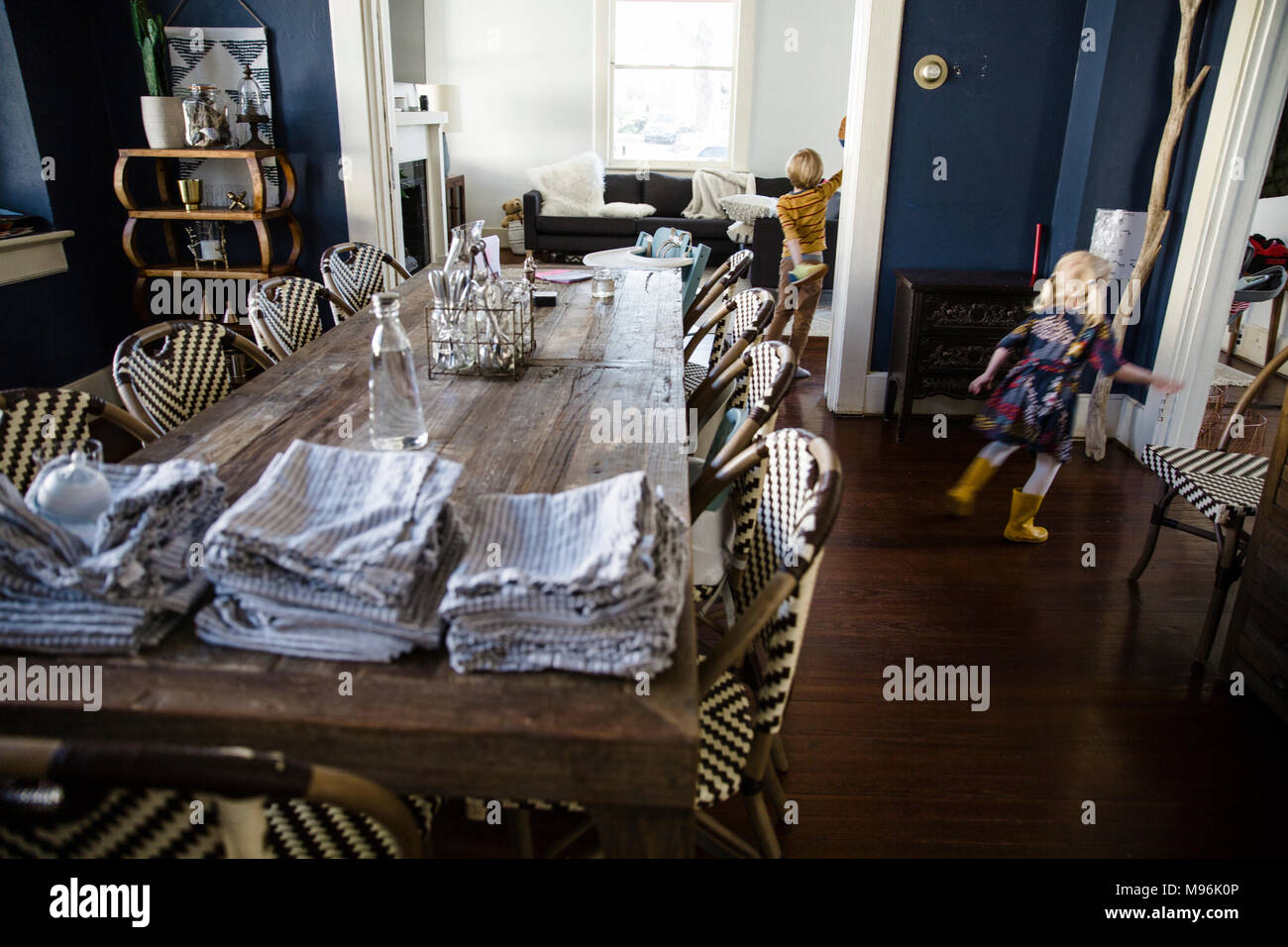Children around dining table with napkins on top - Stock Image