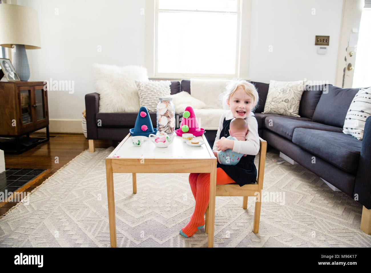 Girl sitting on chair next to table with party hats on - Stock Image