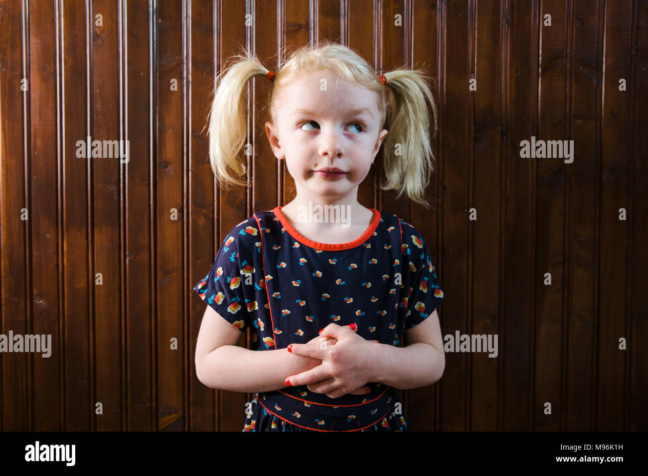 Girl with pigtails pulling faces - Stock Image