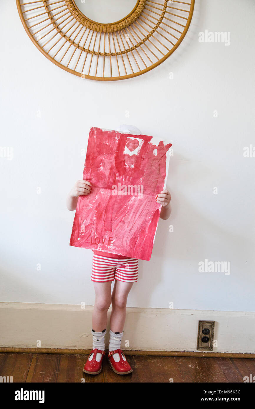 Girl holding up valentines card - Stock Image