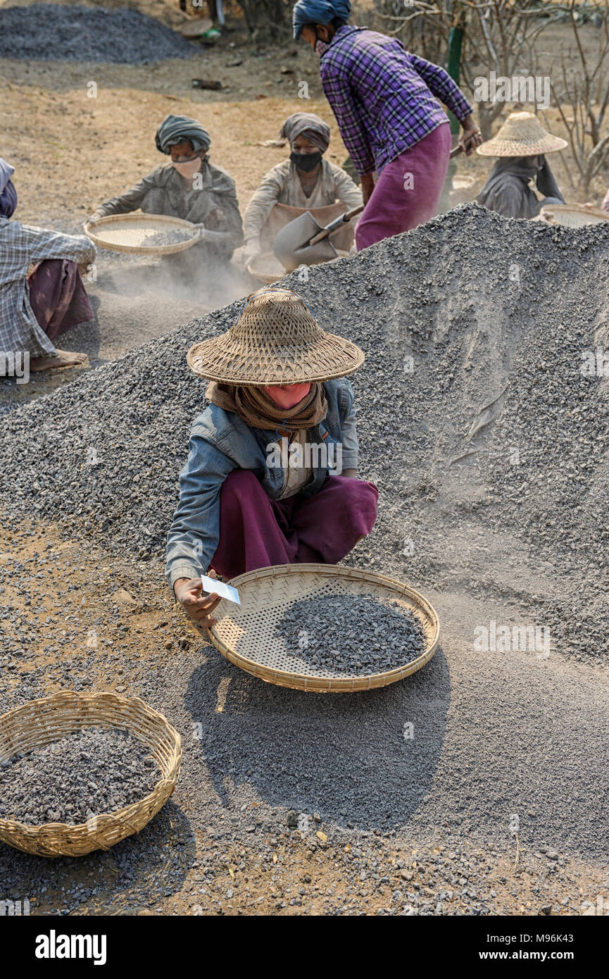 Road construction in Myanmar.Women on a road construction crew, sifting gravel near Bagan - Stock Image