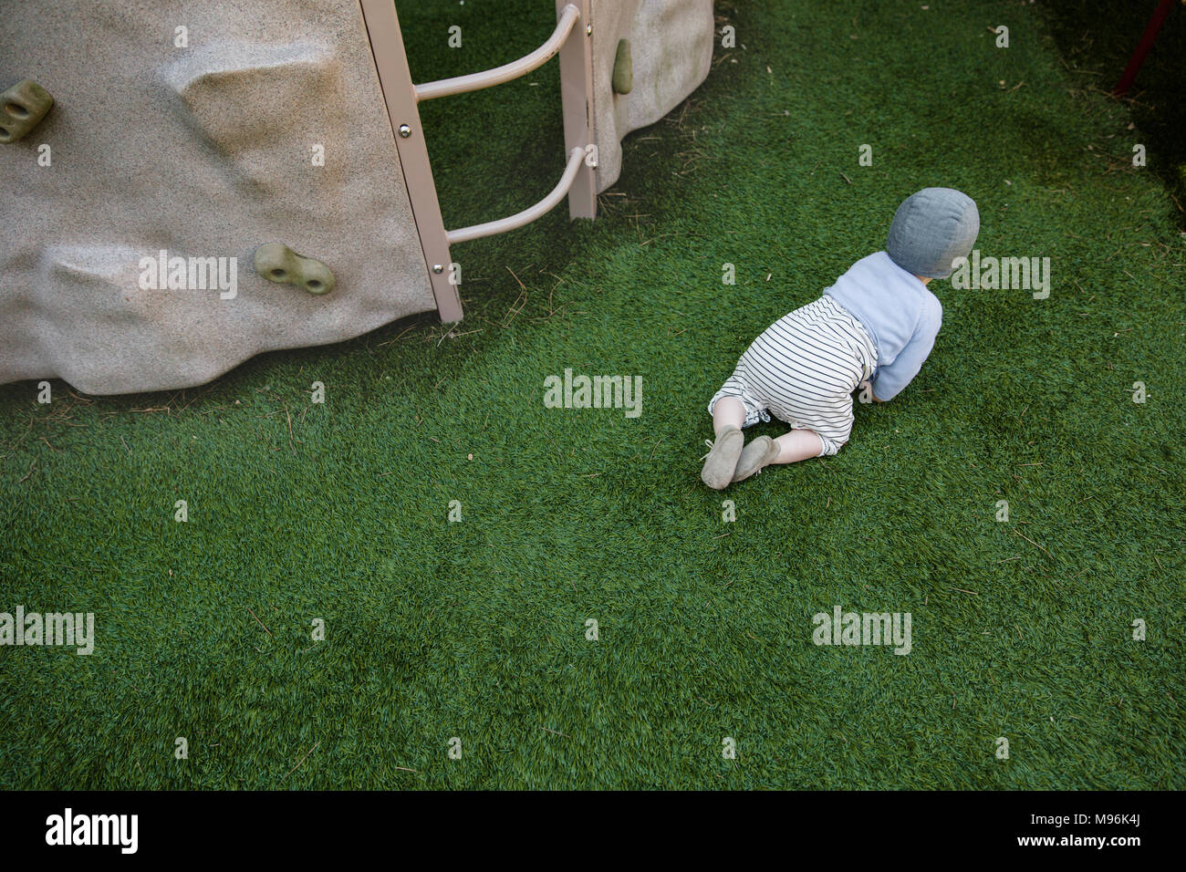 Baby crawling on grass - Stock Image