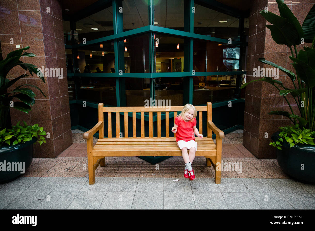 Girl in red shirt sitting on wooden bench - Stock Image