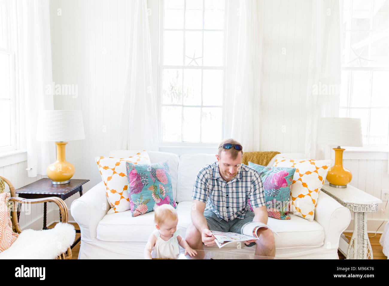 Man with sunglasses reading next to baby - Stock Image