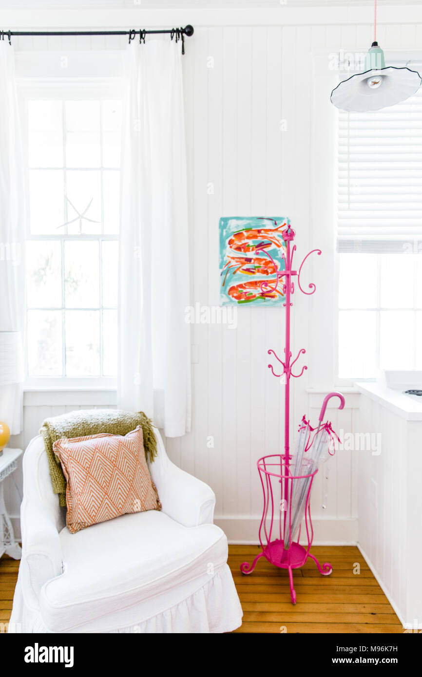 White chair next to pink coat hooks in white home - Stock Image