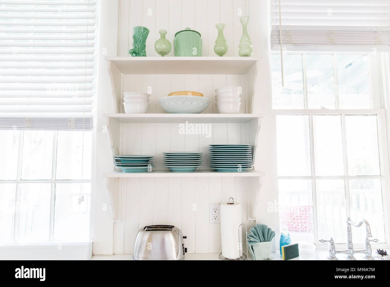 Kitchen shelves with green plates/bowls and toaster - Stock Image
