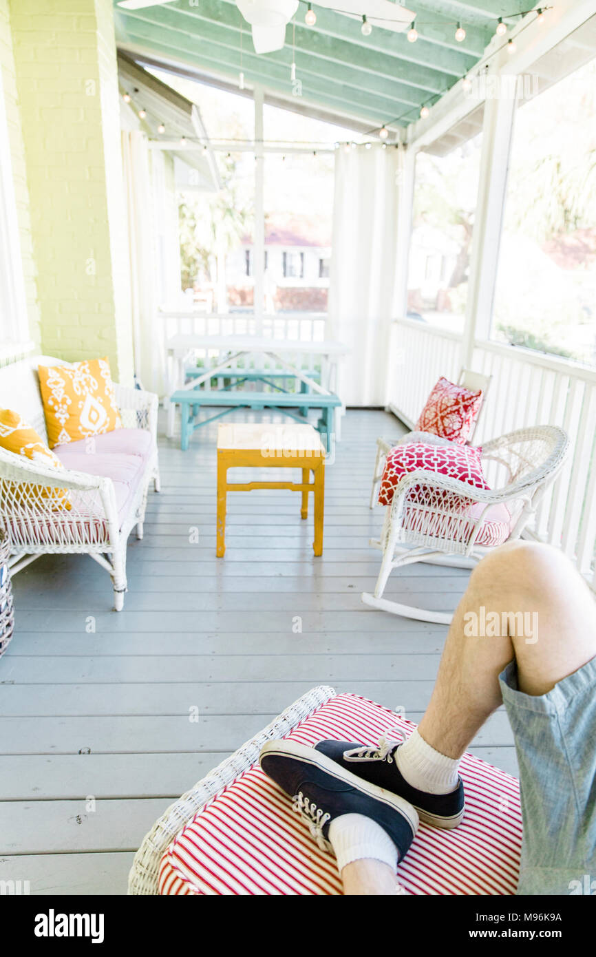 Man laying down on porch - Stock Image