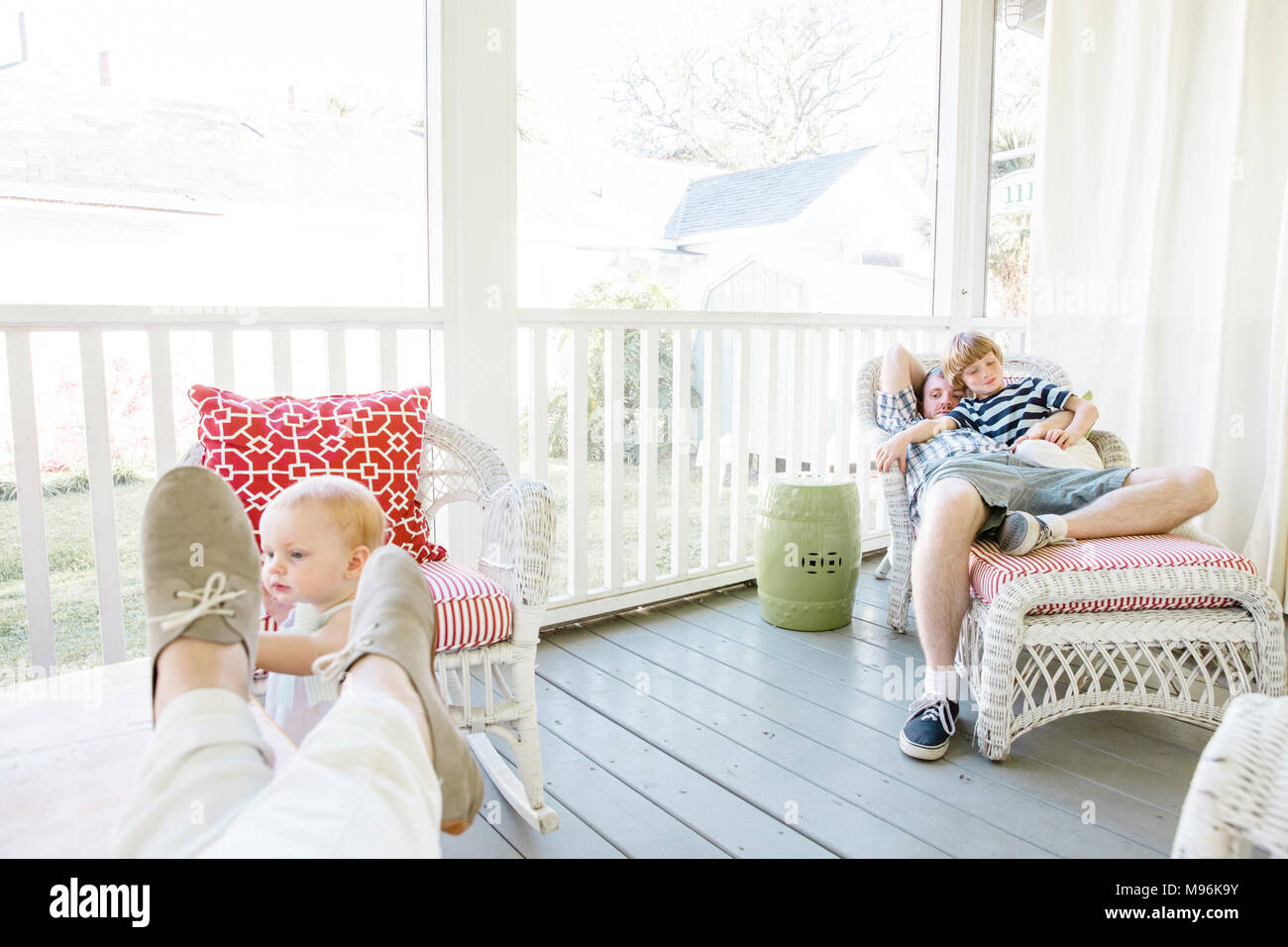 Family relaxing on porch - Stock Image