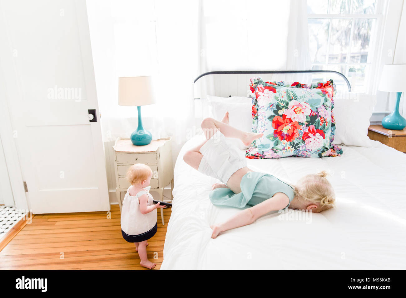 Girl laying on bed with baby next to her - Stock Image