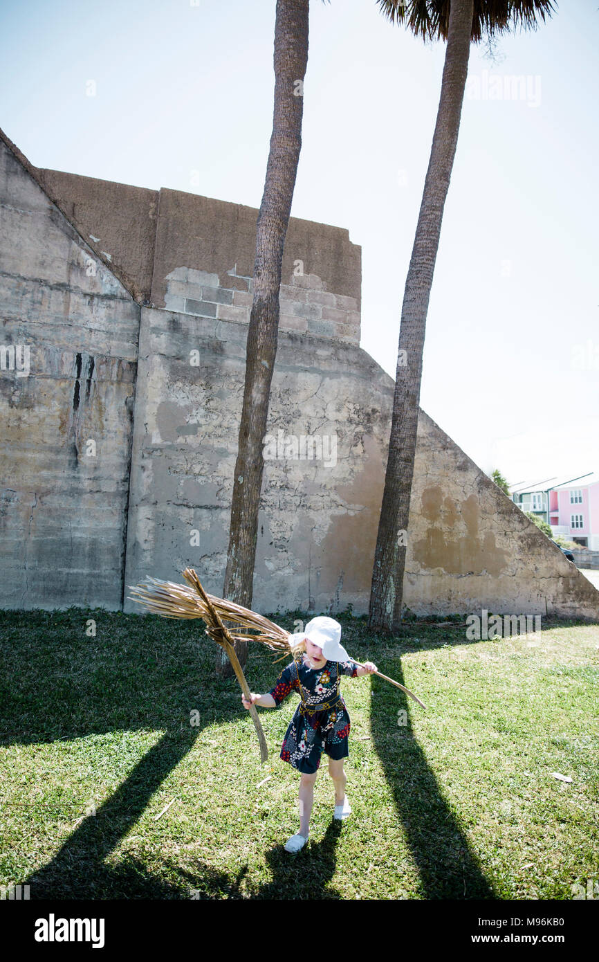 Girl playing with palm branches next to palm trees - Stock Image