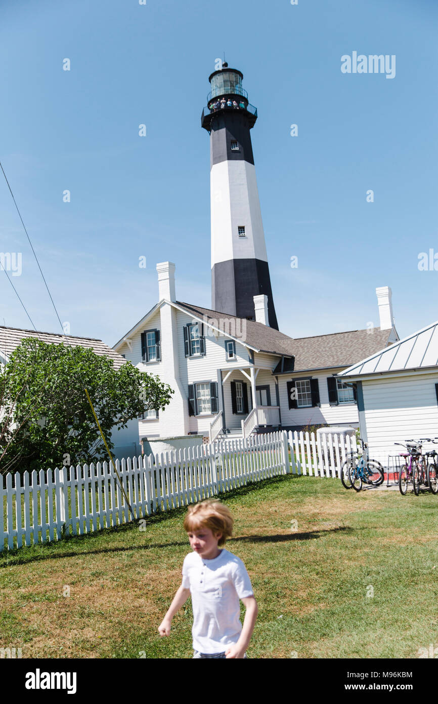Family outside next to white fence and lighthouse - Stock Image
