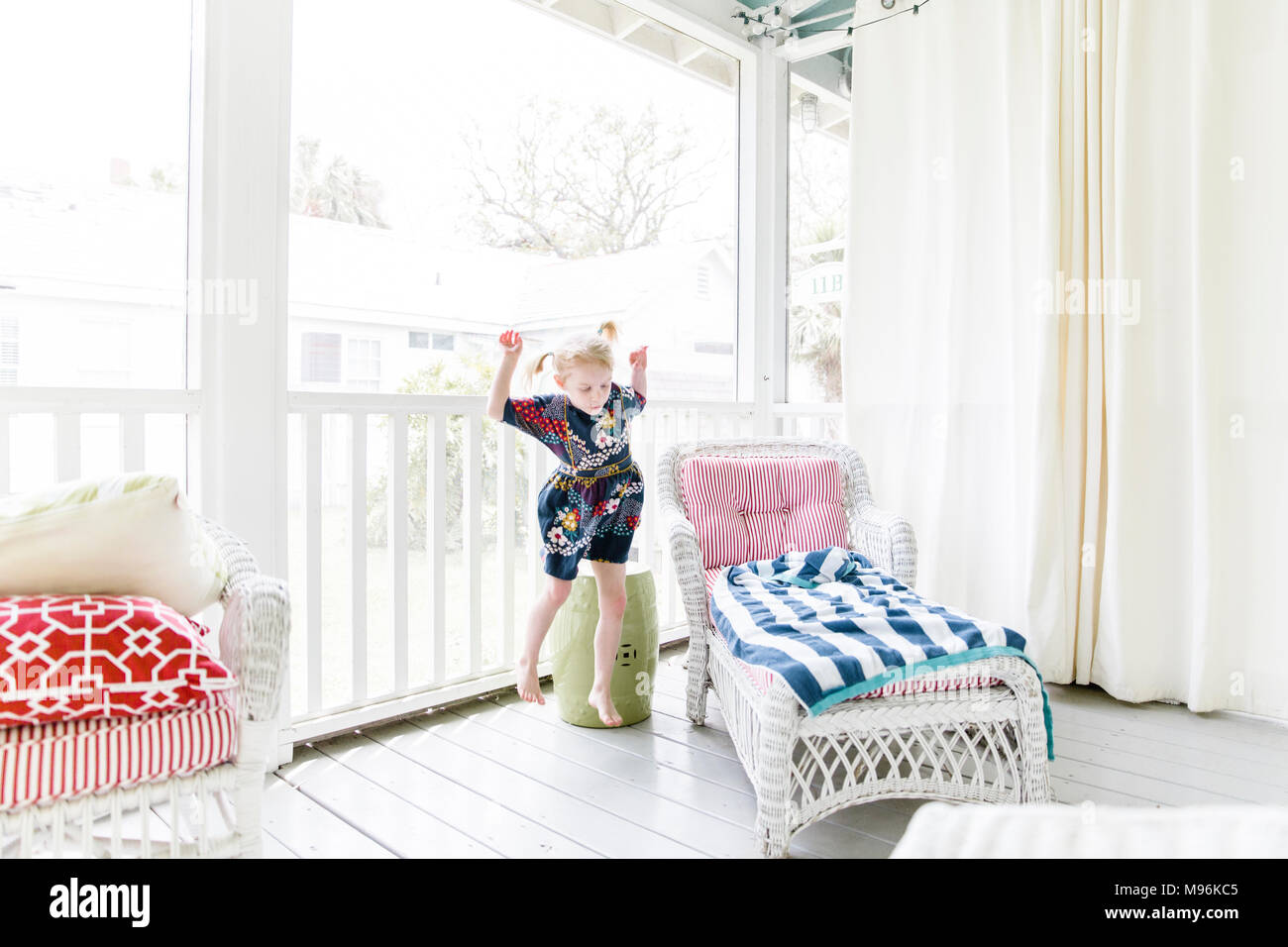 Girl alone playing on porch - Stock Image