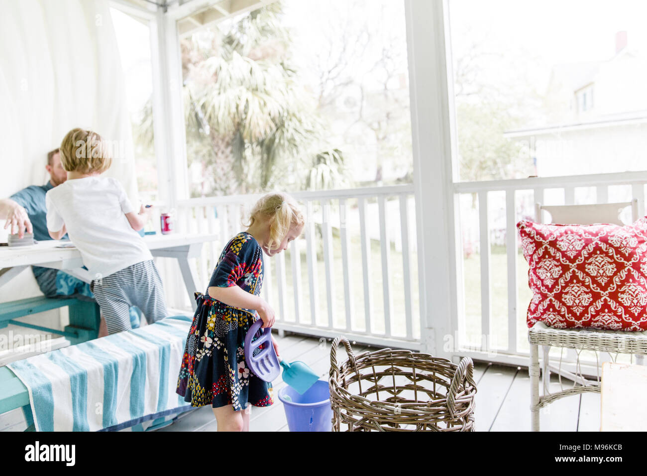 Family sitting/standing on porch - Stock Image