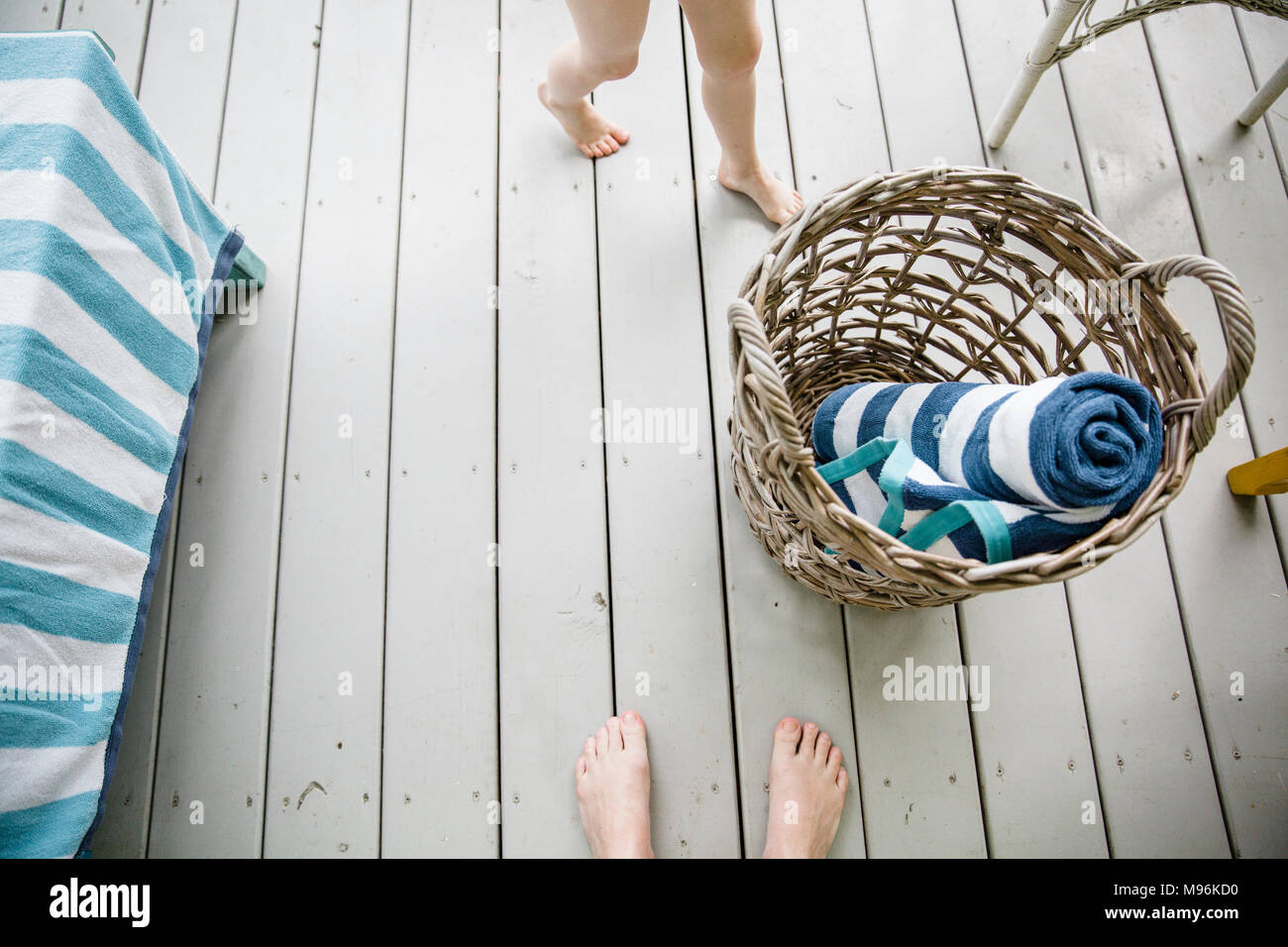 Wicker basket with towels next to children's feet - Stock Image