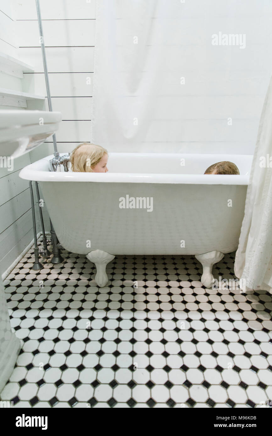 Brother and Sister playing in bathtub - Stock Image