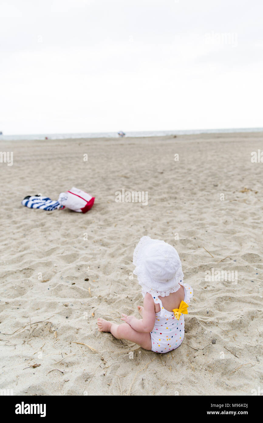 Baby sitting on beach looking out at the sea - Stock Image
