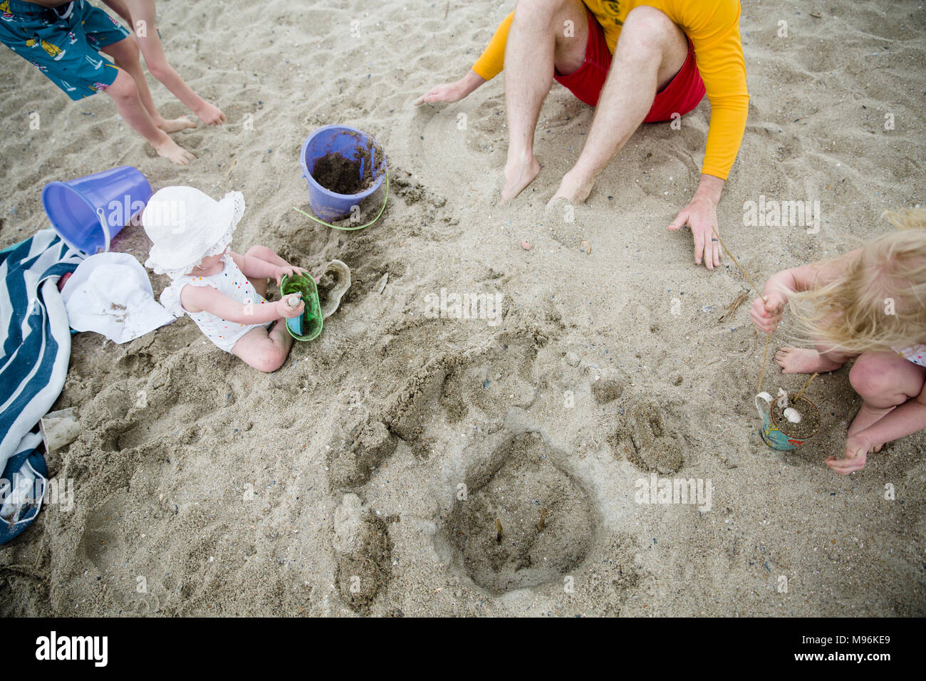 Baby with family sitting on beach - Stock Image