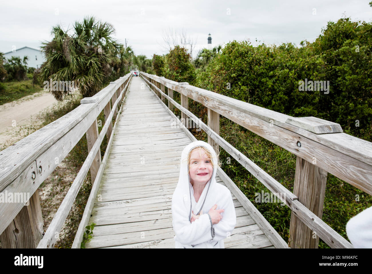 Girl alone smiling at camera on dock/walkway - Stock Image