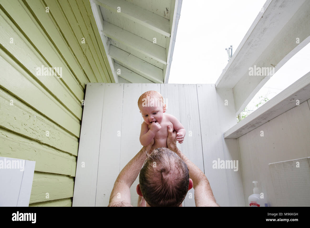 Man holding up baby - Stock Image