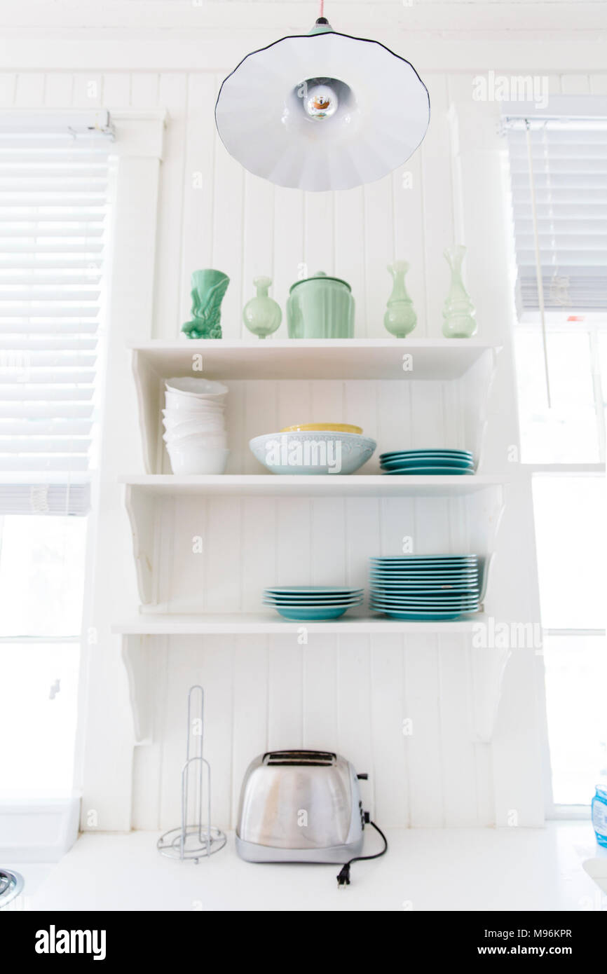 Kitchen shelves with plates, bowls and toaster - Stock Image