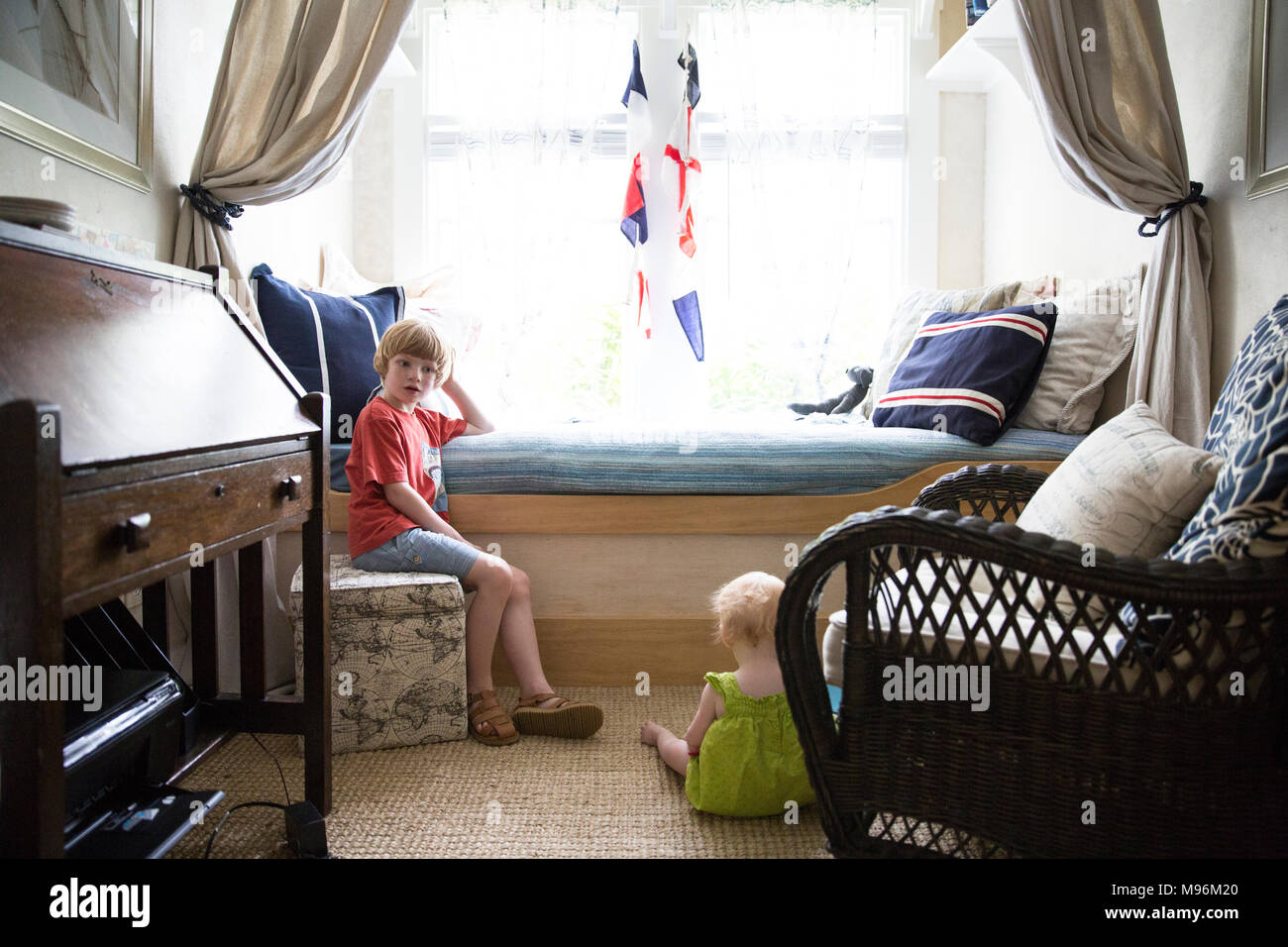 Boy and baby in nautical style bedroom Stock Photo
