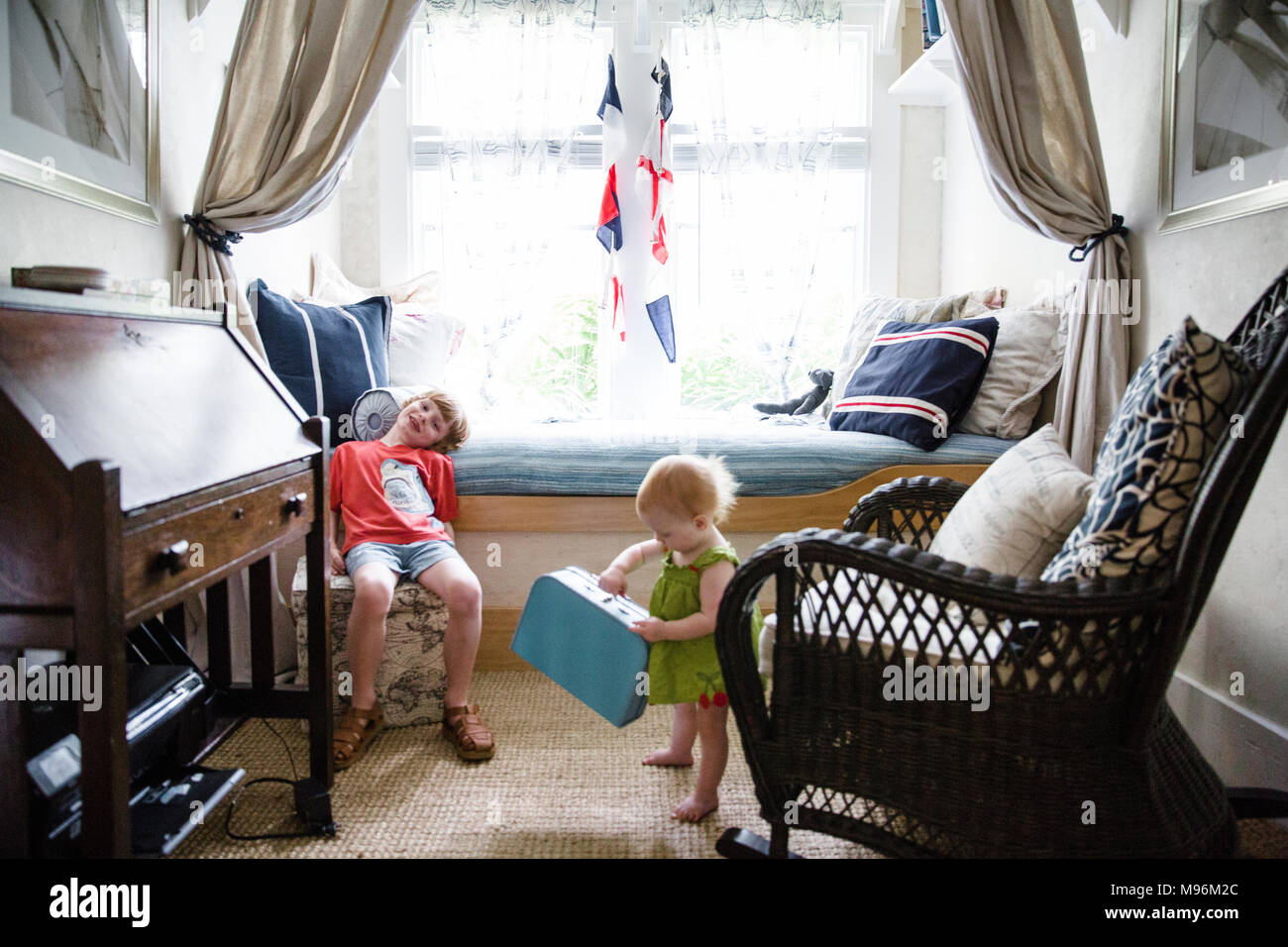 Boy and baby in nautical style bedroom - Stock Image