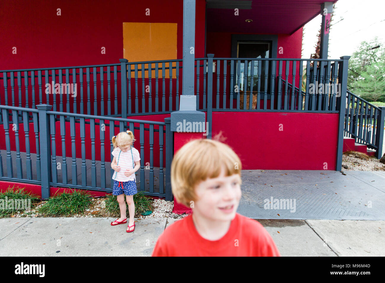 Brother and Sister outside of red building - Stock Image