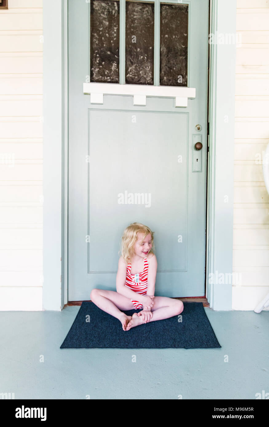 Girl smiling/sitting outside of door - Stock Image