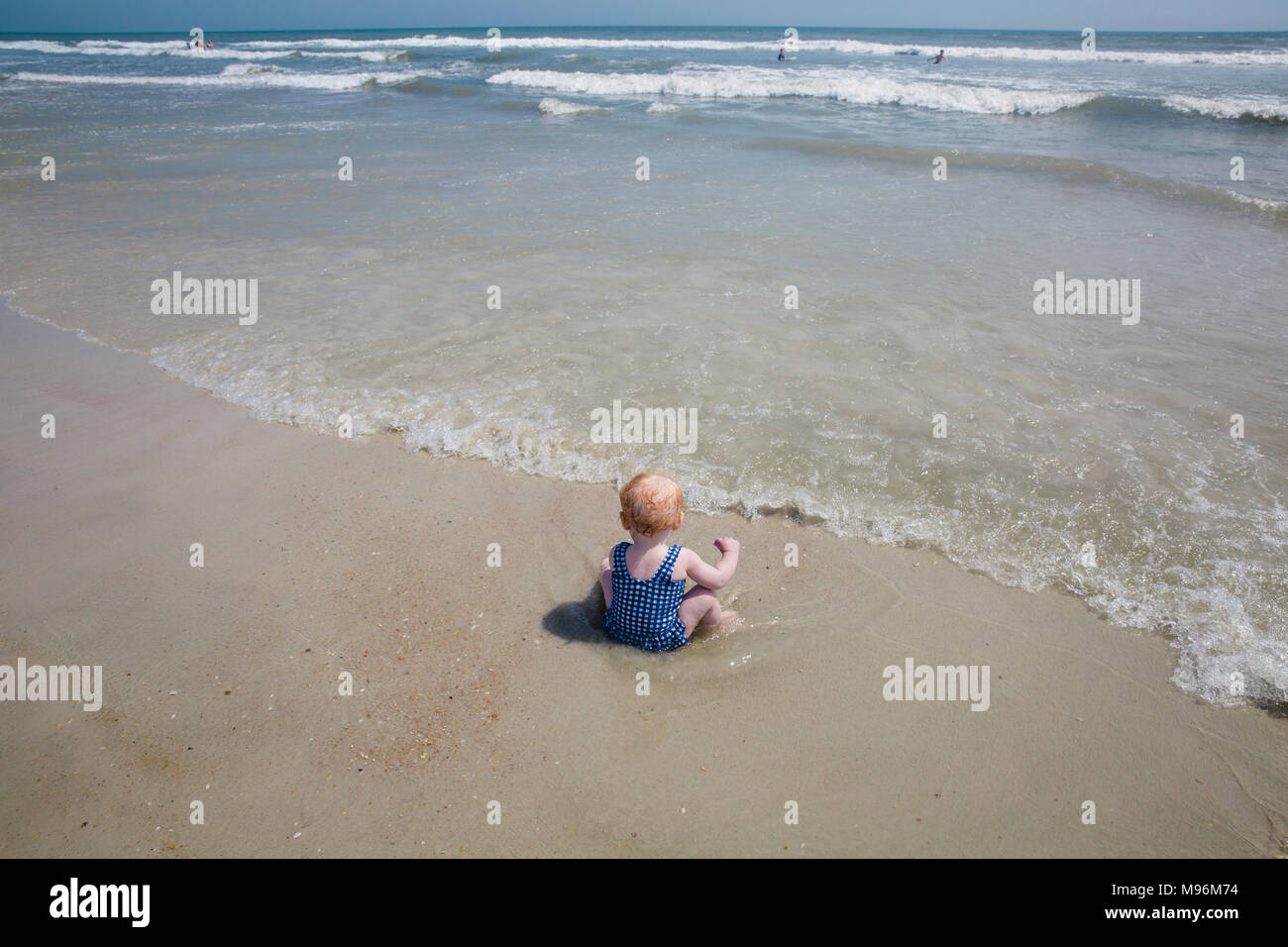 Baby sitting in water on beach - Stock Image