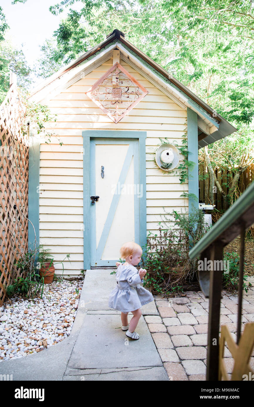 Girl in garden next to shed - Stock Image