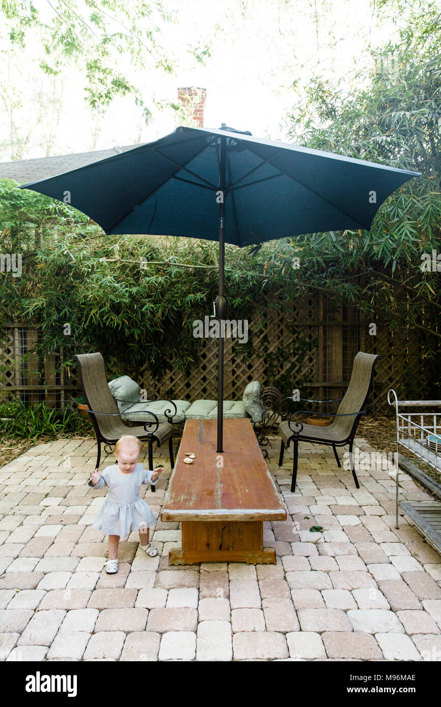 Baby walking outside garden with chairs and umbrella - Stock Image