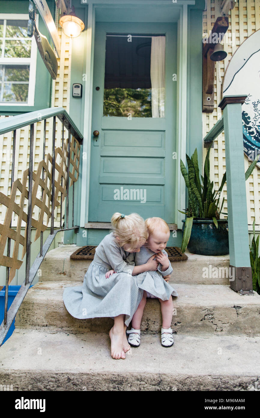 Girl and baby sitting outside on steps - Stock Image