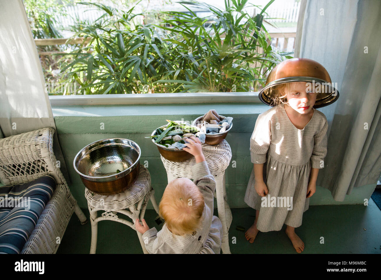 Girl with bowl on head in home - Stock Image