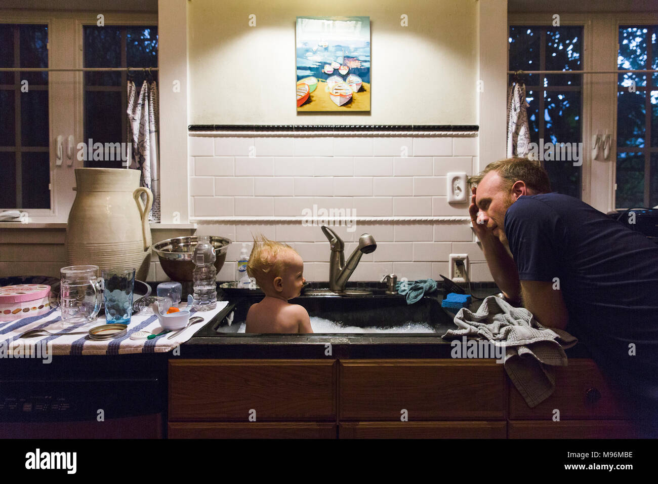 Father washing baby in sink - Stock Image