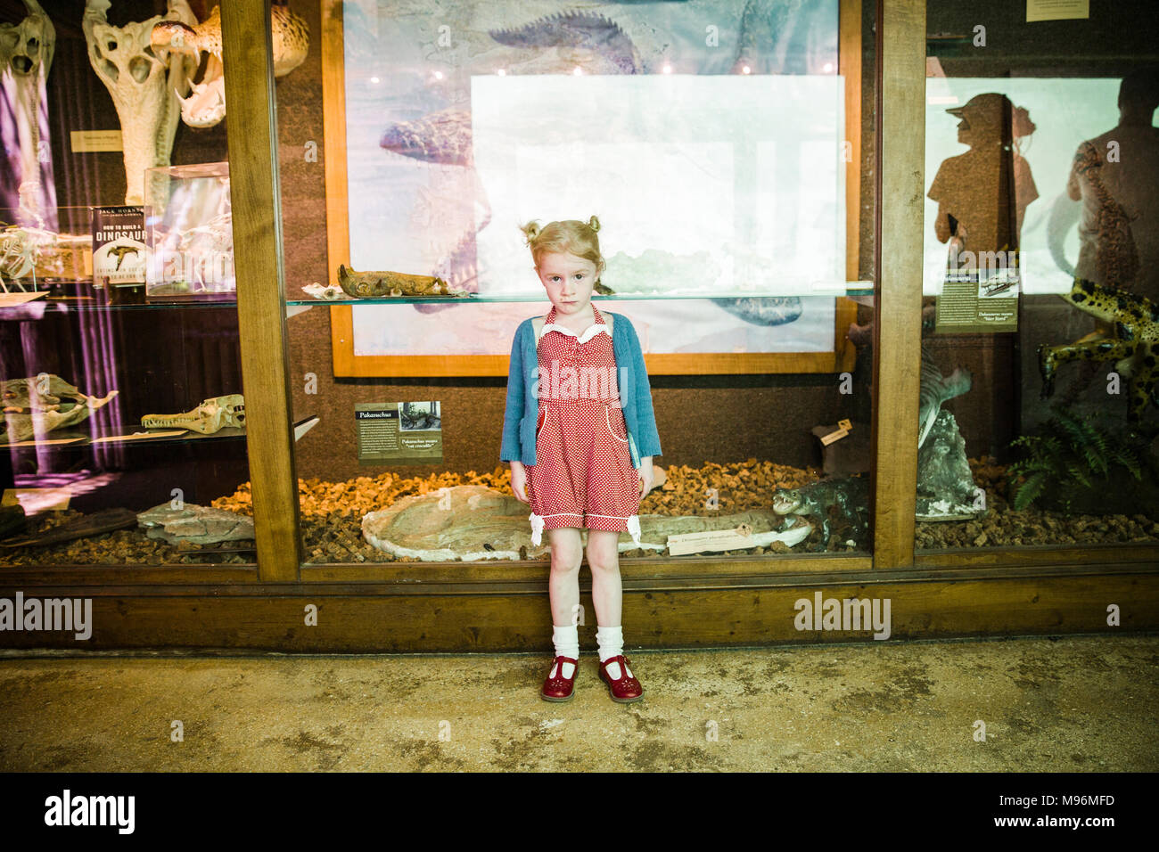 Girl standing next to museum exhibit - Stock Image