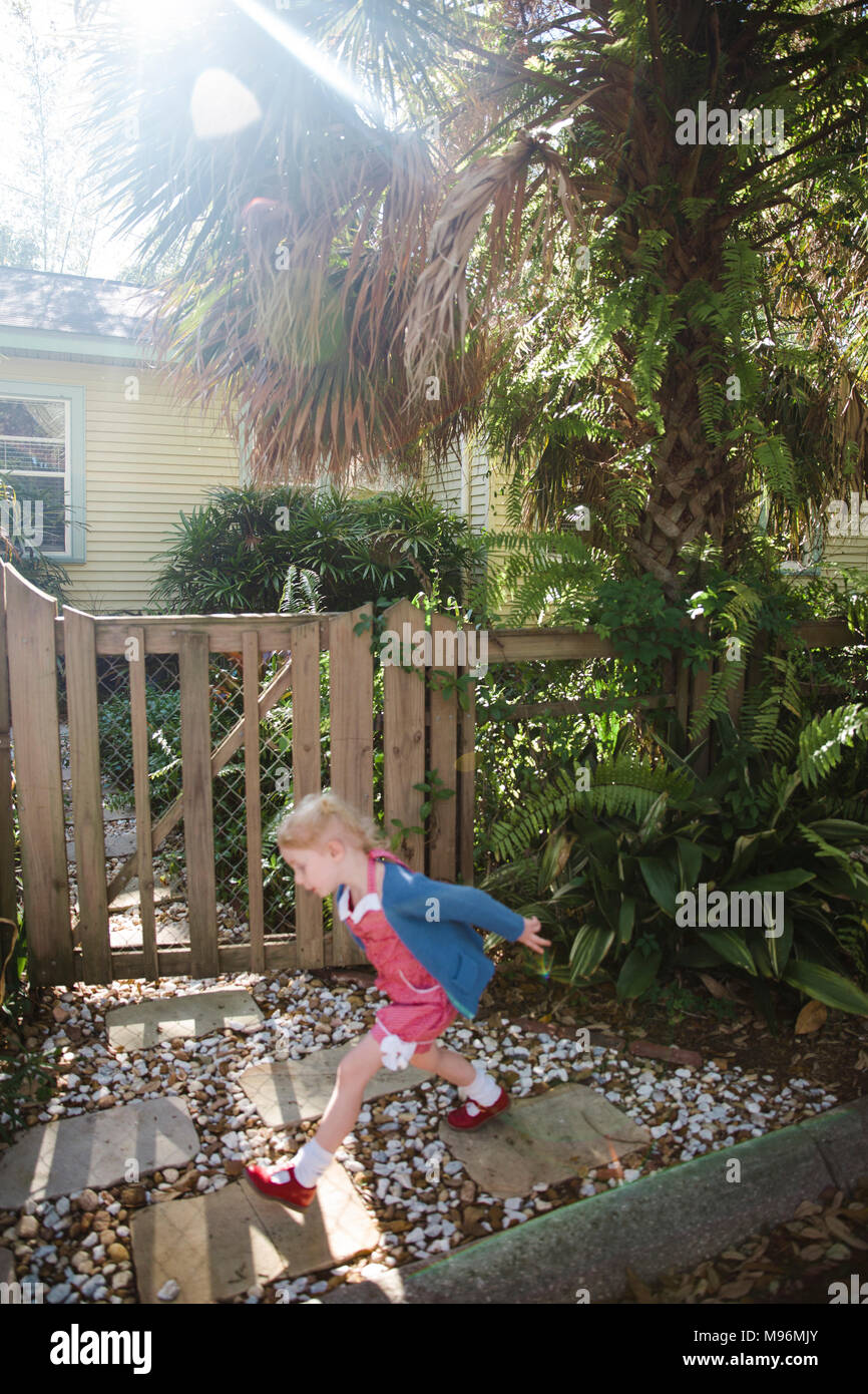 Girl stepping stones outside home - Stock Image