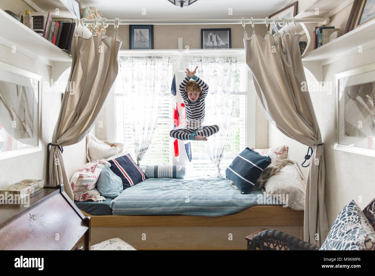 Boy jumping on bed Stock Photo