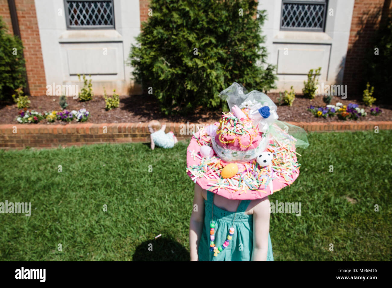 Girl with Easter hat on next to baby - Stock Image