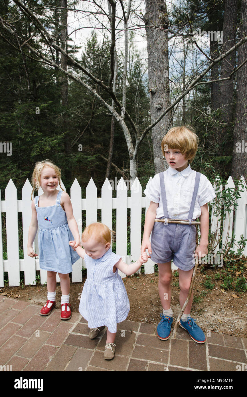 Two children holding babies hands next to white fence - Stock Image
