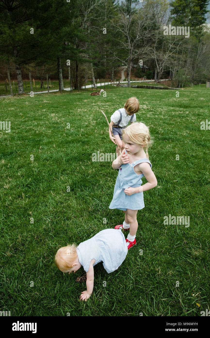Baby and two children in field - Stock Image