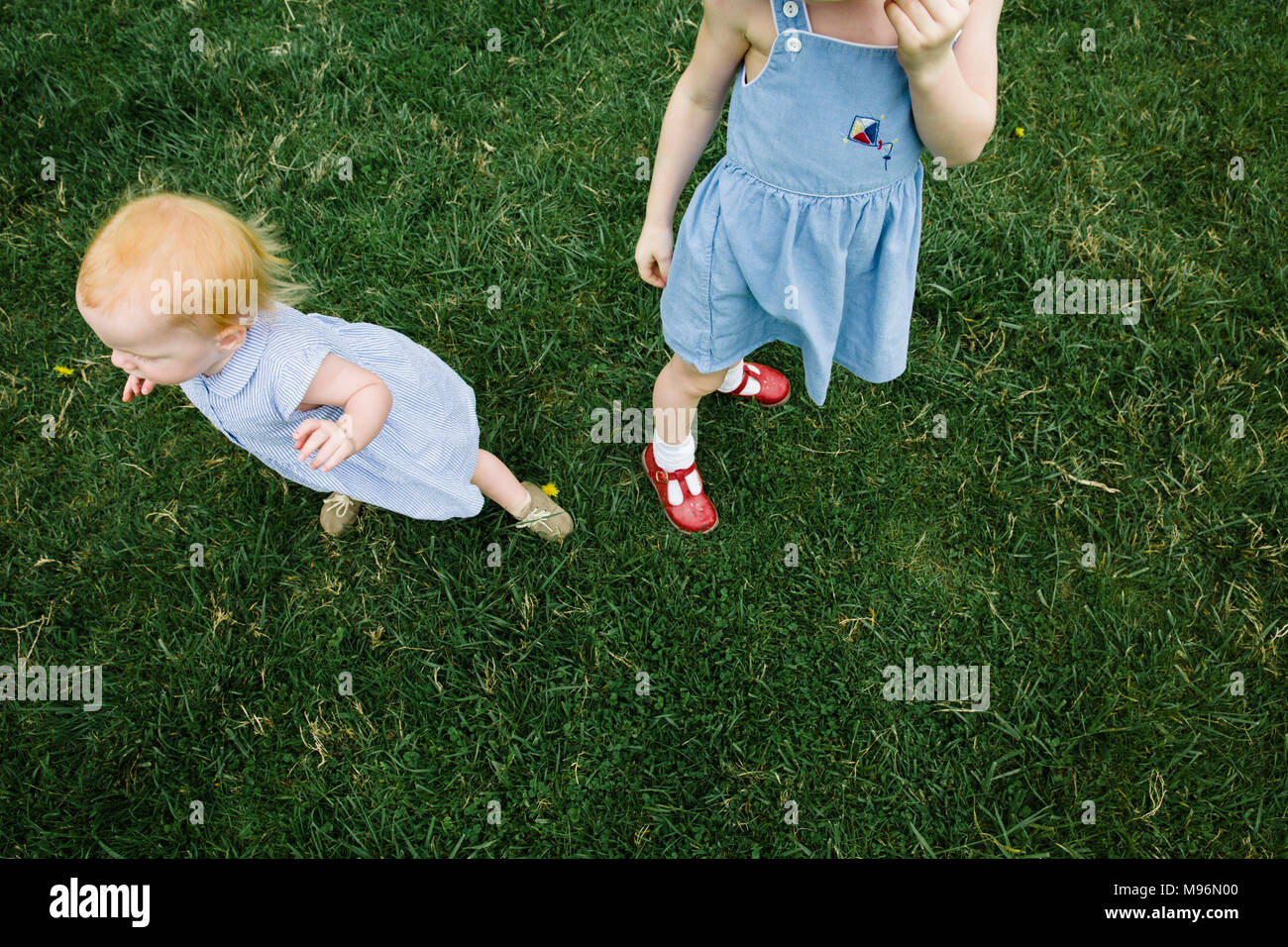 Baby and girl standing in field - Stock Image