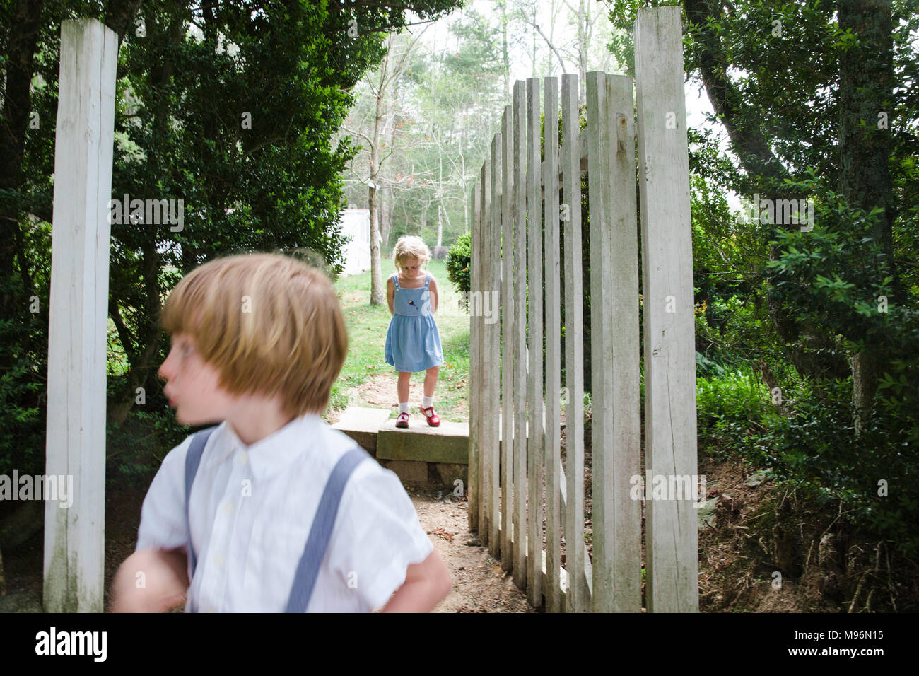 Two children wander around gate Stock Photo